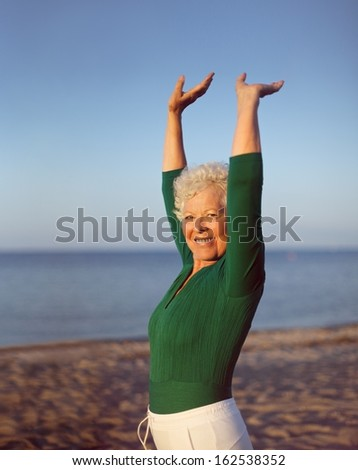 Portrait of healthy senior woman practicing yoga on beach with copyspace. Old caucasian woman exercising outdoors to stay fit. Health and fitness concept. - stock photo