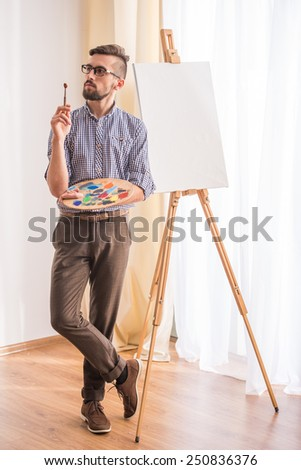 Portrait of highly gifted painter is holding brush in his hand is going to paint a picture. - stock photo