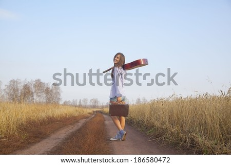Portrait of hippie latin hispanic Woman walking on way between golden wheat field and blue sky background with acoustic Guitar on his shoulder and old retro suitcase in the other hand