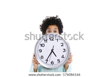 portrait of hispanic business woman hiding behind big watch and looking at camera with worried expression. Isolated on white background