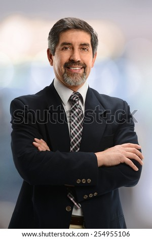 Portrait of Hispanic businessman smiling isolated inside office building - stock photo