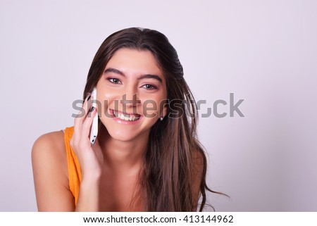 Portrait of hispanic / caucasian young woman using a mobile phone. Woman talking on the phone, isolated over grey brackground. - stock photo