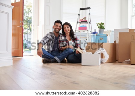 Portrait Of Hispanic Couple Moving Into New Home - stock photo