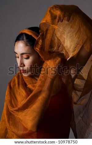Portrait of hispanic dancer with orange veil - stock photo