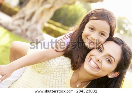 Portrait Of Hispanic Mother And Daughter In Park - stock photo