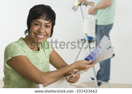 Portrait of Hispanic woman holding paint swatches - stock photo