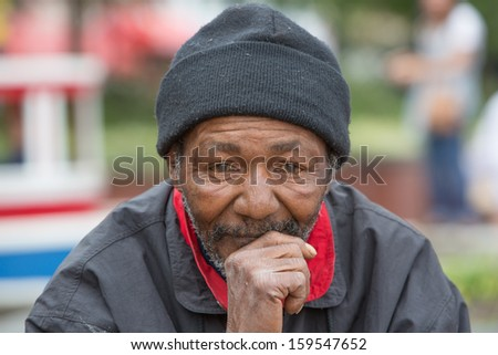 Portrait of homeless man thinking while sitting outdoors during the daytime - stock photo