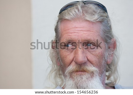 Portrait of homeless man with beard outside