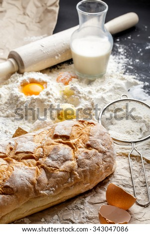 portrait of homemade bread, yolk, flour, and milk - stock photo