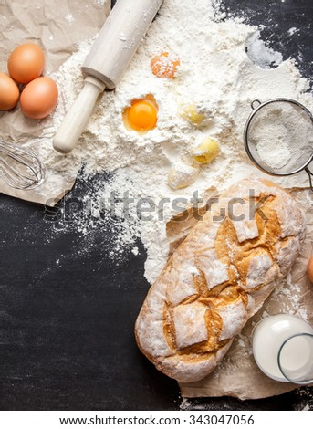 portrait of homemade gluten free bread with ingredients on black board with copy space - stock photo