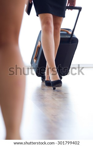 Portrait of hostess legs with luggage in airport. - stock photo