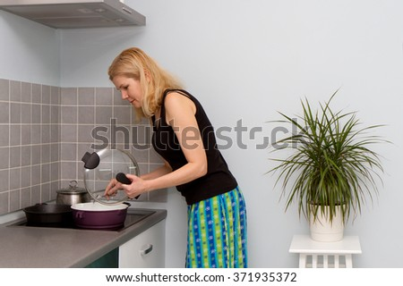Portrait of housewife at domestic kitchen - stock photo