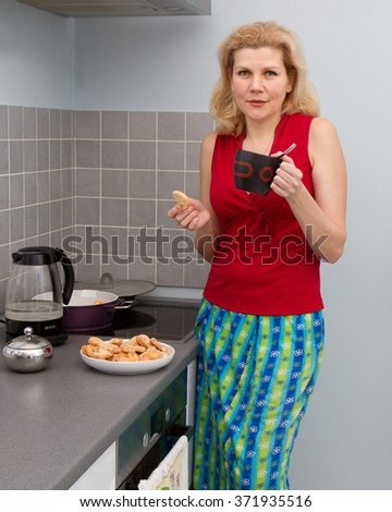 Portrait of housewife drinking tea and cooking supper at domestic kitchen - stock photo