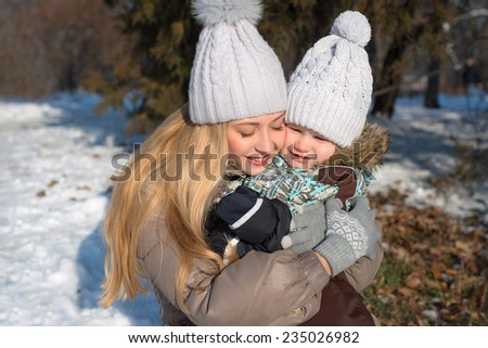 Portrait of hugging mother and baby in winter park - stock photo