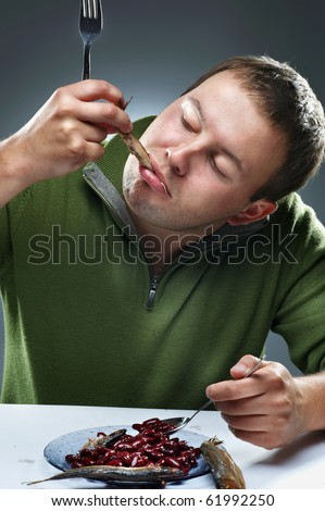 Portrait of hungry man eating fish - stock photo