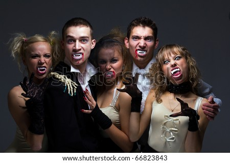 Portrait of hungry vampire family on a gray background - stock photo