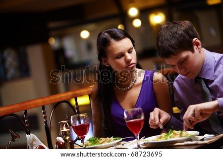 Portrait of hungry woman looking at man?s food in cafe - stock photo