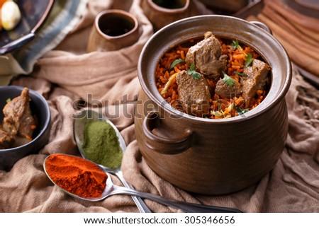 portrait of indian dum biryani lamb served in a pot - stock photo