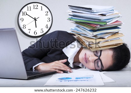 Portrait of indian entrepreneur sleeping in the office with paperwork over her head - stock photo