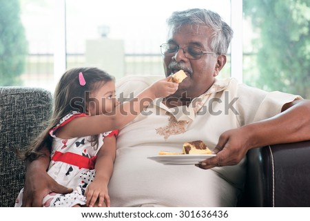 Portrait of Indian family at home. Grandchild feeding butter cake to grandparent. Grandfather and granddaughter. Asian people living lifestyle. - stock photo