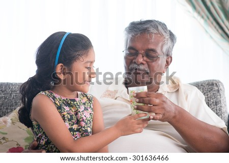 Portrait of Indian family at home. Grandchild giving a glass water to grandparent . Asian people living lifestyle. Grandfather and granddaughter.