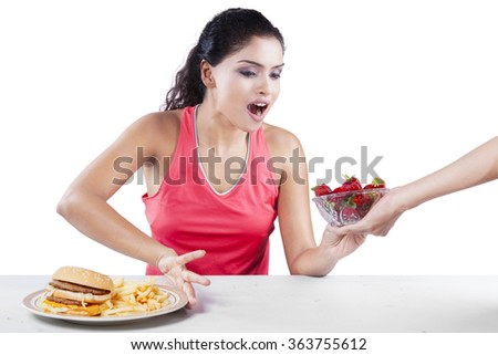 Portrait of indian girl with strawberry rejecting hamburger, isolated on white background - stock photo
