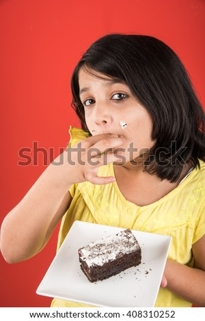 portrait of Indian kid eating cake or pastry, cute little girl eating cake, girl eating chocolate cake over red background