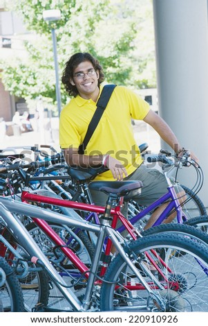 Portrait of Indian man leaning on bicycle - stock photo