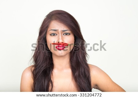 Portrait of Indian woman holding chili pepper as her mustache