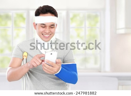 portrait of injured young man look happy play smartphone with copy space on his left side - stock photo