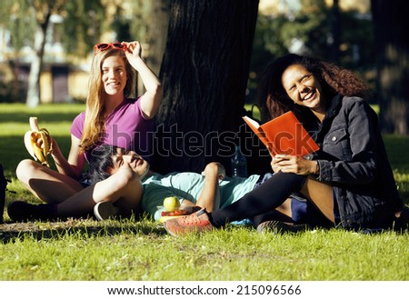 portrait of international group of students close up smiling, blond girl, asian boy, young african woman in green park - stock photo