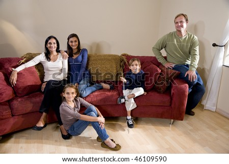 Portrait of interracial family of five sitting on living room sofa at home - stock photo