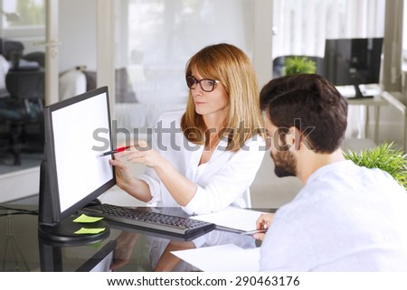 Portrait of investment advisor advise to young businessman to start small business. Middle age professional woman points out to the computer screen.  - stock photo