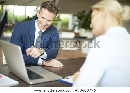 Portrait of investment advisor businesswoman sitting at office in front of computer and consulting with her business client.