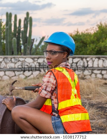 Portrait of Jamaican model wearing construction suit using a hammer to repair a old cannon.  Embracing her African culture in support of National Women's History Day and National Women's Day.