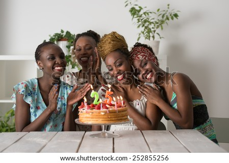 Portrait of joyful african girl looking at birthday cake surrounded by friends at party - stock photo