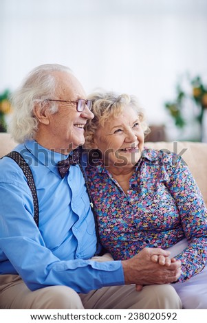Portrait of joyful and affectionate aged couple in smart clothes - stock photo