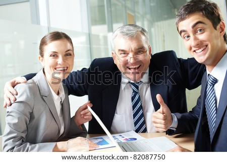 Portrait of joyful business group showing their gladness and looking at camera - stock photo