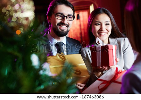 Portrait of joyful colleagues giving xmas presents to their associate - stock photo