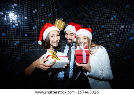 Portrait of joyful colleagues in Santa caps having fun in nightclub  - stock photo