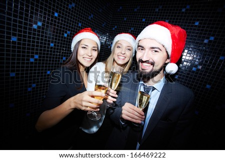 Portrait of joyful colleagues in Santa caps toasting with champagne in nightclub  - stock photo