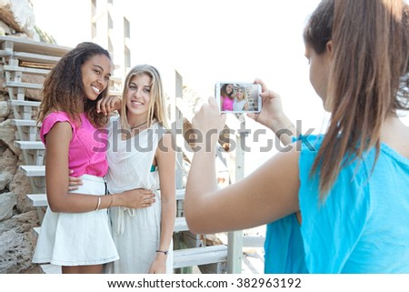 Portrait of joyful diverse teenagers girls friends smiling together taking photos and networking with smart phone, coastal outdoors. Adolescents summer travel lifestyle. Young people using technology. - stock photo