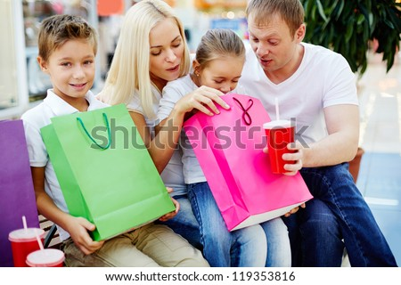 Portrait of joyful family having break and looking through paperbags in the mall - stock photo