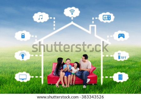 Portrait of joyful family having fun together on the sofa under a design of smart home technology system  - stock photo