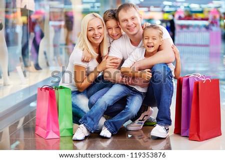 Portrait of joyful family with paperbags looking at camera in the mall - stock photo