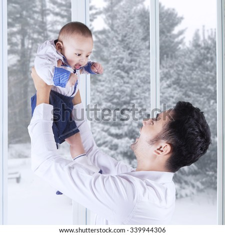 Portrait of joyful father lifting up his male baby at home, shot with winter background on the window - stock photo
