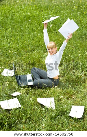 Portrait of joyful female sitting on green grass with raised arms during her work
