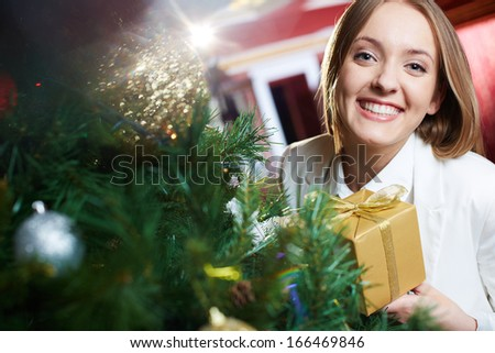 Portrait of joyful female with xmas present looking at camera with smile - stock photo