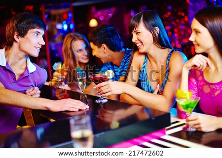 Portrait of joyful friends talking at party in the bar