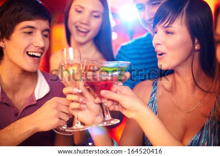Portrait of joyful friends toasting at birthday party with focus on happy girl and guy